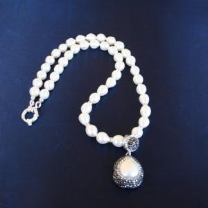 Collana di perle di acqua dolce con intermezzi di cristalli swarovski e pendente di  argento 925 con perla barocca e cristalli swarovski di alta qualità. Chiusura in argento 925.